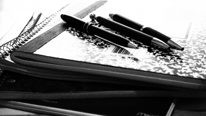 3 pens on a composition book